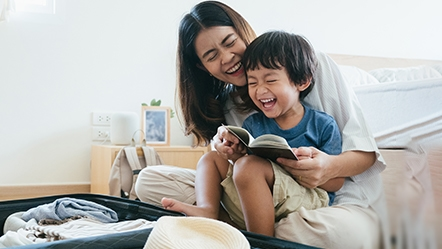 Mother and son reading a book while smiling
